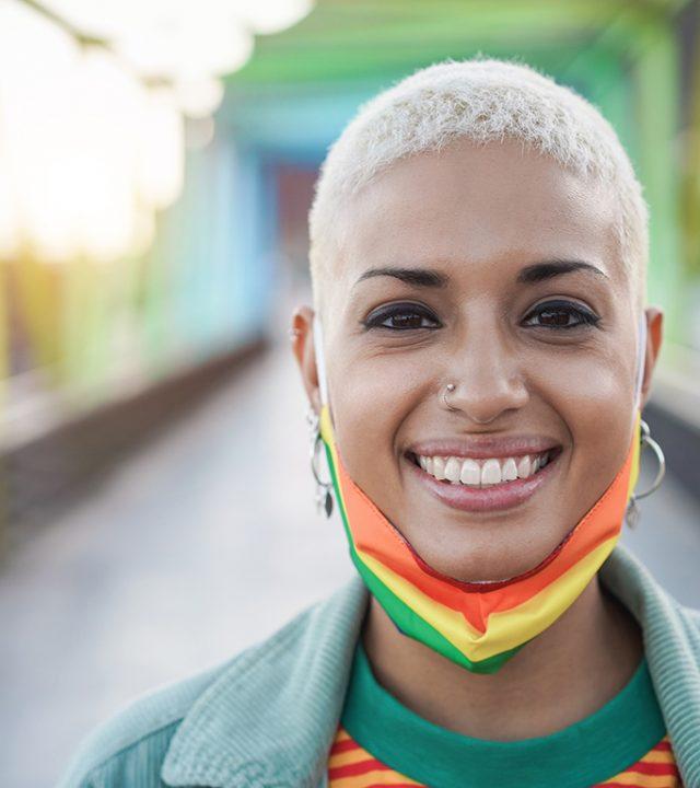 Happy-gay-woman-wearing-LGBT-rainbow-flag-pride-mask